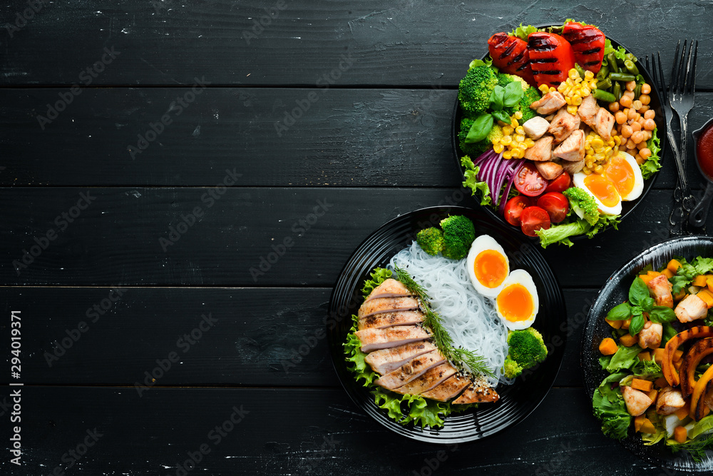 Fototapety, obrazy: Dishes of chicken meat and vegetables in a black plate on a black background. Buddha bowl. Top view. Free space for your text.