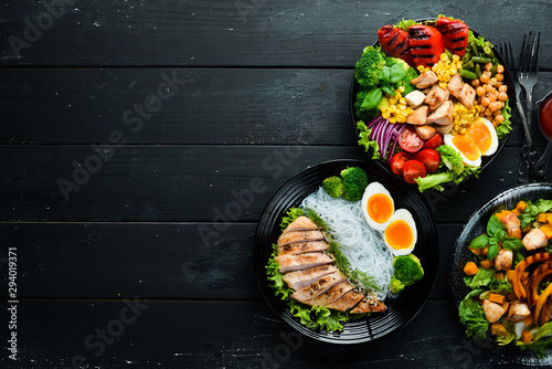 Dishes of chicken meat and vegetables in a black plate on a black background. Buddha bowl. Top view. Free space for your text. - 294019371