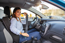 Safety First. Beautiful Caucasian Lady Fastening Car Seat Belt. Pretty Young Woman Driving Her New Car. Pretty Young Woman Driving Her New Car. Female Fastening Safety Belt In Car