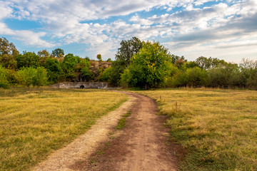Fototapeta na wymiar Dirt road leading to the Sanctuary of the Nymphs and Aphrodite near the village of Kasnakovo, Municipality of Dimitrovgrad, Haskovo Province, Southern Bulgaria