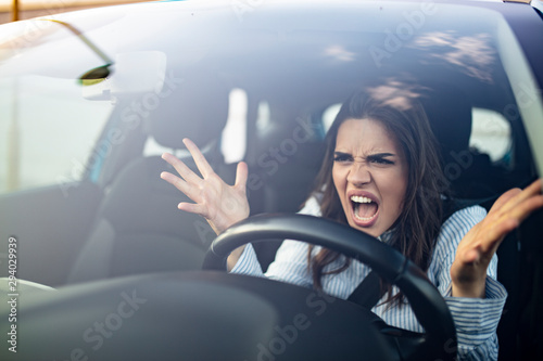 Fotografie, Tablou  Closeup portrait, angry young sitting woman pissed off by drivers in front of her and gesturing with hands