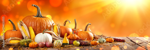 Obraz Wooden Harvest Table With Pumpkins Corncobs Gourds And Apples With Orange Bokeh And Sunlight Background - fototapety do salonu