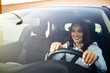 Beautiful Smiling woman driving car, attractive girl sitting in automobile, outdoors summer portrait. Young woman driving her car. Young woman in car driving seat looking ahead, close up