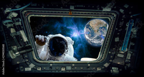Leinwand Poster astronaut knocking and the earth Elements of this image furnished by NASA