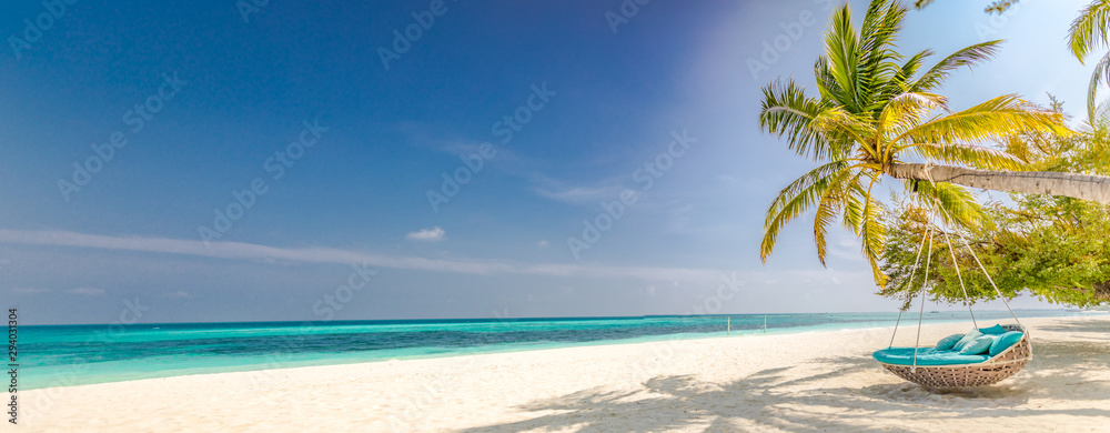 Fototapeta Tropical beach panorama as summer landscape with beach swing or hammock and white sand and calm sea for beach banner. Perfect beach scene vacation and summer holiday concept. Boost up color process