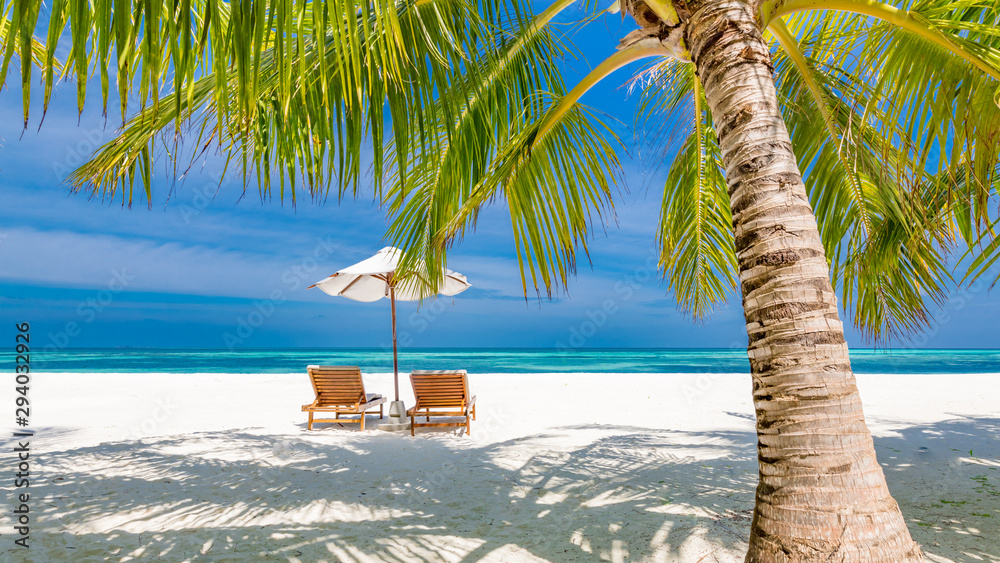 Fototapeta Beautiful tropical sunset scenery, two sun beds, loungers, umbrella under palm tree. White sand, sea view with horizon, colorful twilight sky, calmness and relaxation. Inspirational beach resort hotel