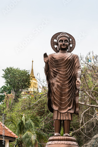 Valokuvatapetti Si Racha, Thailand - March 16, 2019: Closeup of Giant bronze statue of enlightened, compassionate bodhisattva with halo on Ko Loi Island under silver sky with green foliage