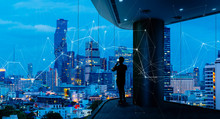 Businessman Standing Using Smart Phone In Modern Space Watching City Night View.Business With Ambition And Vision Concept.and Wireless Network Low Poly Line.