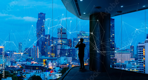 Businessman standing using smart phone in modern space watching city night view.Business with ambition and vision concept.and wireless network low poly line. - 294038395