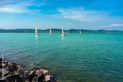Obraz na płótnie Sail Boats on the blue Lake Balaton Hungary with rocks on the coast