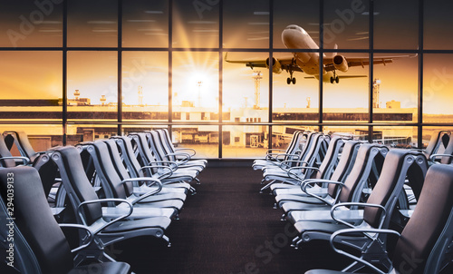 Poster Avion à Moteur Empty airport terminal lounge with airplane on background. Modern airport waiting area with flyinf airplane and seats. Lounge and travel concept.