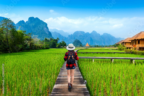 Tourism with backpack walking on wooden path, Vang vieng in Laos. Canvas Print