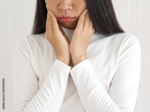 Valokuva  trigeminal neuralgia and temporomandibular joint and muscle disorder in asian woman, She use hand touching her cheek and symptoms fo pain and suffering on isoleted white background