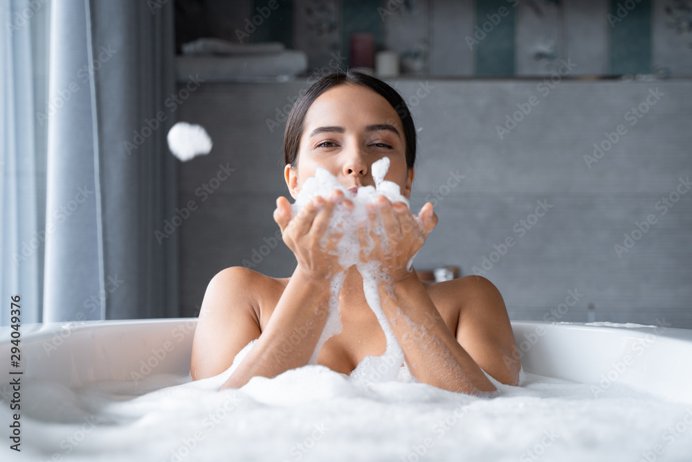 Fototapeta Relaxed young woman taking a bath with foam