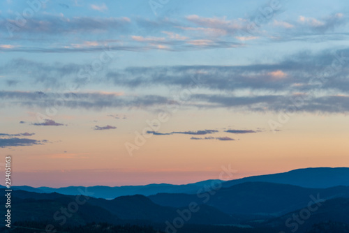 Aluminium Prints Blue Tranquil evening landscape with blue mountains and pastel sunset colors and cirrus clouds