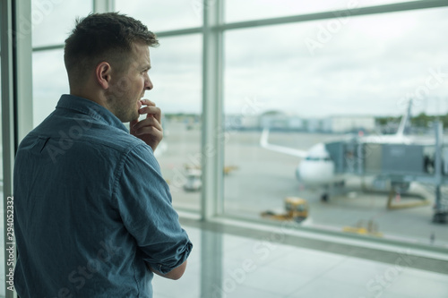 Caucasian young man is afraid to flight standing in terminal near window Wallpaper Mural