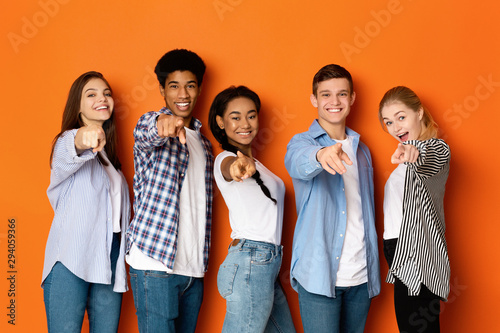 Happy teenagers pointing fingers at camera and smiling Wallpaper Mural