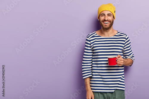 Fototapeta Smiling young man holds red mug, drinks hot beverage, wears yellow hat and casual striped sweater, has glad expression, enjoys spare time, isolated over purple background, blank space for your promo obraz