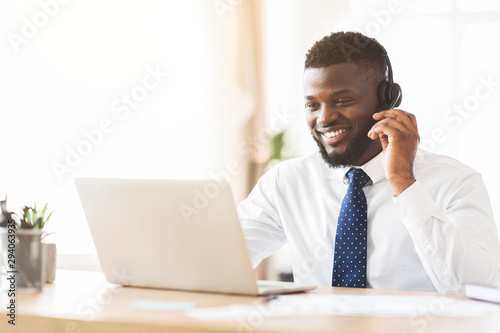 Fototapety, obrazy: Happy consultant with headset looking at laptop