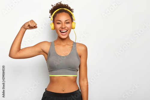 Horizontal view of dark skinned woman in good mood, raises arm with muscles, has strong body, dressed in gym outfit, listens audio via modern headphones, poses indoor. Fitness and music concept