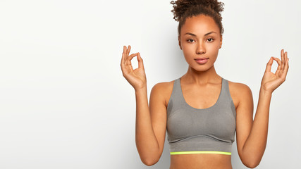 Cropped image of curly calm young woman poses in lotus pose, meditates and has yoga practice, looks directly at camera, wears sport bra, isolated over white background, free space on left side