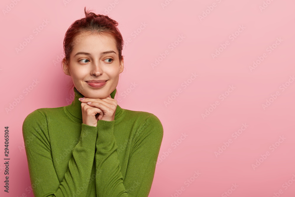 Fototapeta Photo of thoughtful pleasant looking European girl keeps both hands under chin, looks away, imagines something positive, dressed in green casual jumper, isolated on pink wall, free space aside