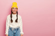 Portrait of happy Asian girl looks gladfully aside, has pleasant smile, dressed in yellow headgear, white sweater and jeans, has rouge cheeks and makeup, poses over rosy wall, free space on right side