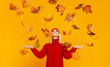 canvas print picture happy emotional cheerful girl laughing  with autumn leaves and knitted autumn red cap  on colored yellow background.