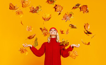 Happy Emotional Cheerful Girl Laughing  With Autumn Leaves And Knitted Autumn Red Cap  On Colored Yellow Background.