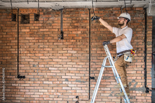 Obraz Electrician with tools, working on a construction site. Repair and handyman concept. - fototapety do salonu