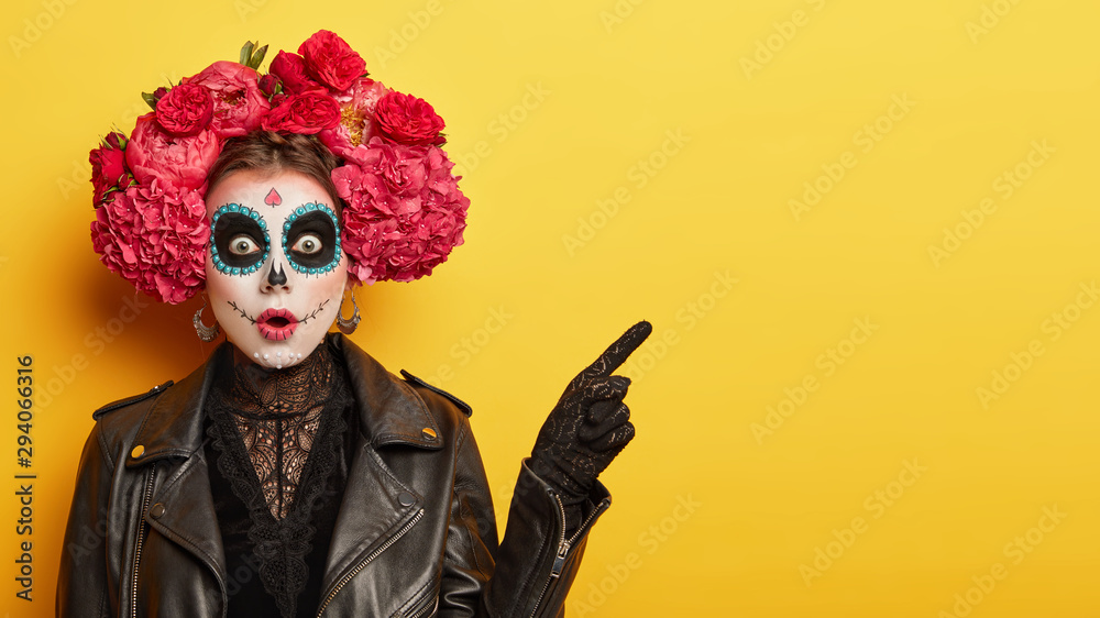 Fototapeta Happy Halloween concept. Scared horrible female in special outfit, wears white clay skull, professional makeup to look spooky, wears black clothes points away on blank space against yellow background