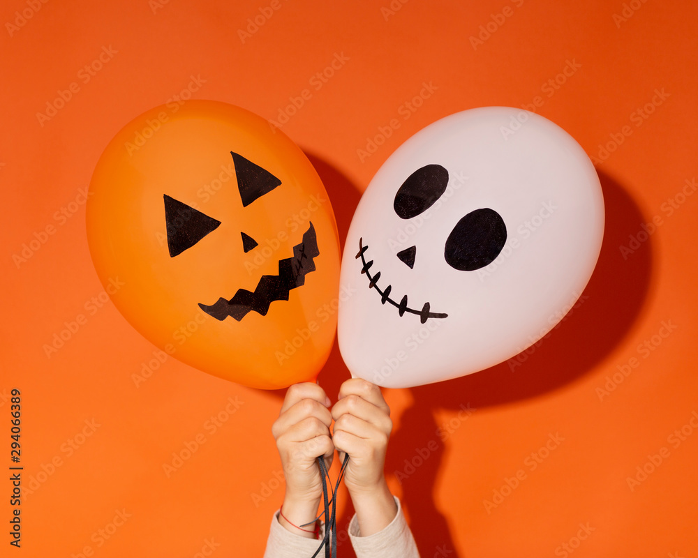Fototapeta Halloween balloons with funny faces in woman hands