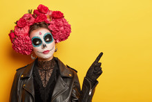Face Art And Traditional Mexican Holiday Concept. Serious Young Lady Wears Dead Mask Skull Makeup, Flower Wreath With Strong Scent To Guide Souls From Cemetries, Points On Free Space Over Yellow Wall