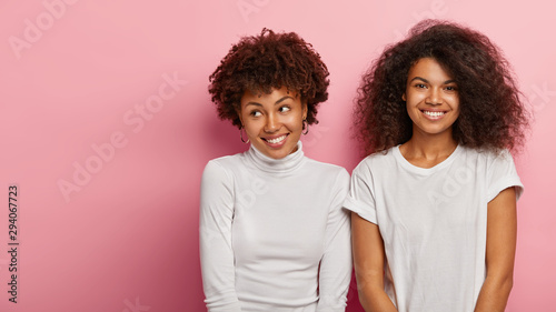 Fotografie, Tablou Portrait of two Afro woman with curly hair, being in high spirit, smile pleasantly, stand next to each other, wear white t shirt, turtleneck, look alike, expresses good emotions