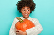 canvas print picture - Satisfied Afro girl embraces big orange pumpkin, bites lips, wears knitted white sweater, has autumn mood, looks aside, isolated over blue background. Holidays, Halloween and Thanksgiving concept