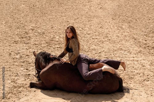 Valokuvatapetti photo girl rider lies with a horse in the sand