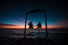 Couple Contemplating An Amazing Sunset At Holbox Island In The Caribbean Ocean Of Mexico