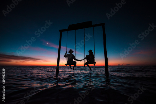 Obraz Couple contemplating an amazing sunset at Holbox Island in the Caribbean Ocean of Mexico - fototapety do salonu