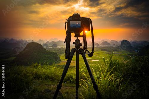 Obraz Camera on tripod and photography view camera with blurred focus landscape of sunset sunrise sun light sky cloud - fototapety do salonu