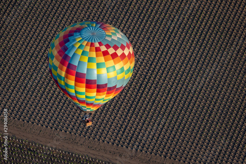 A colorful hot air balloon flies high in the sky early in the morning at sunrise above the Napa Valley, California, known for its vineyards and wineries in addition to ballooning.