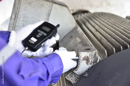 Fototapeta Inspector using a Handheld Vibration Tester  for checking bearings and overall vibration of motor