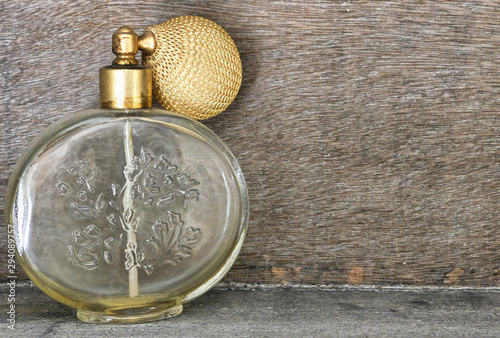Antique glass perfume bottle to the side, with wooden background Wallpaper Mural