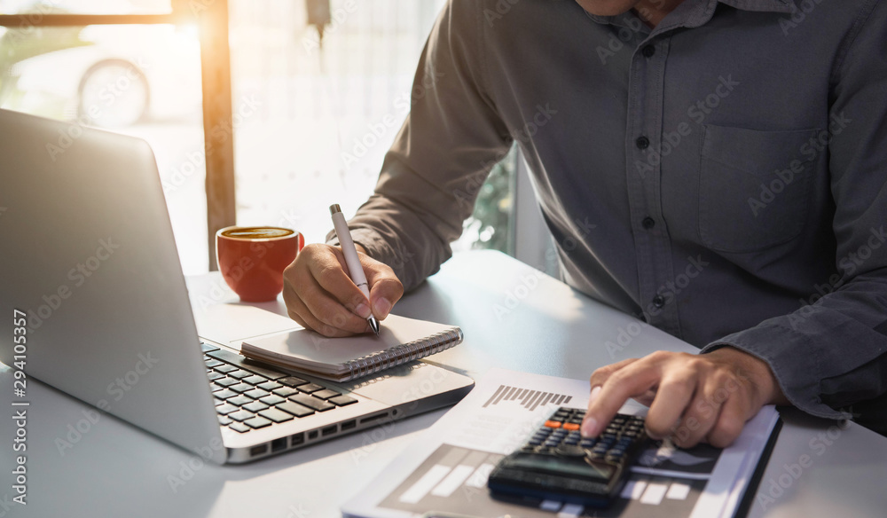 Fototapeta Male businessman working on desk office with using a calculator to calculate the numbers, finance accounting concept.
