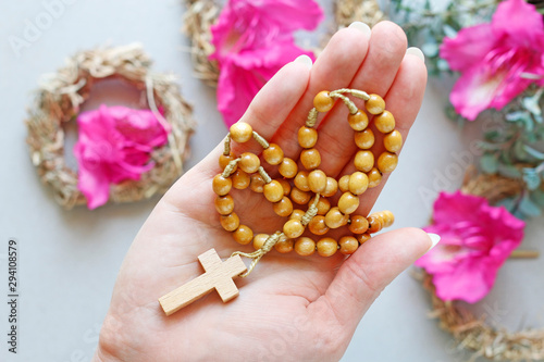 Woman holds wooden rosary in her hand Fototapeta