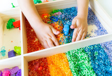 Sensory Box With Rainbow Rice Inside. Montessori Material Baby