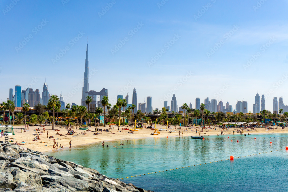 Fototapeta Beach in Dubai with people and skyscapers in the background