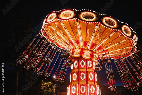 Foto auf Gartenposter Vergnugungspark Illuminated swing chain carousel in amusement park at the night