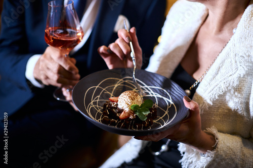 Fototapeta High european cuisine. People eat sweet dessert from beautiful dish and drink red champagne. Restaurant concept obraz