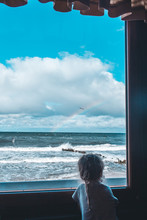 Lone Little Girl Standing On Window In Front Of The Sea And Looking To It. Sky Is Blue And Waves On A Sea.