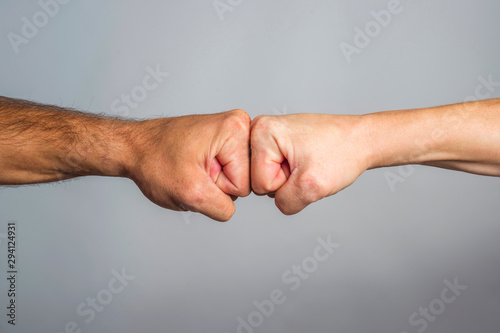 Fotografiet  Two male fists hitting each other